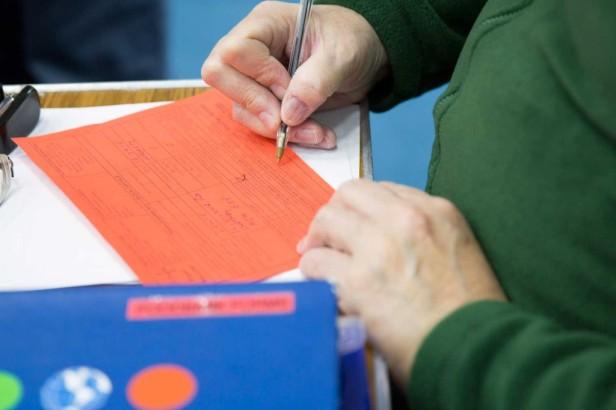 volunteer-writting-on-red-voucher-1024x683