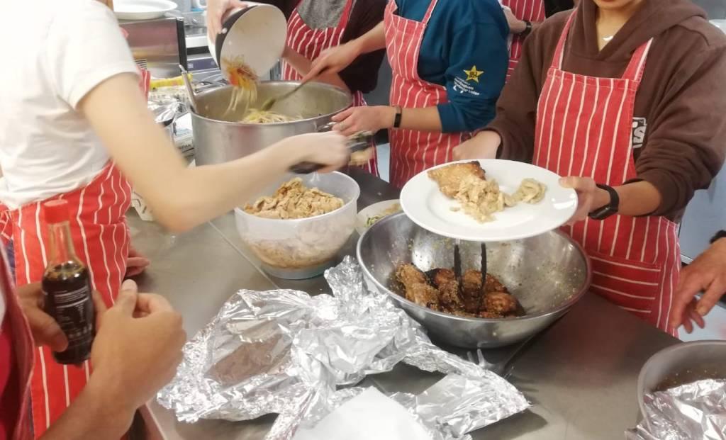 Volunteers serving food at Tasty Tuesdays meal